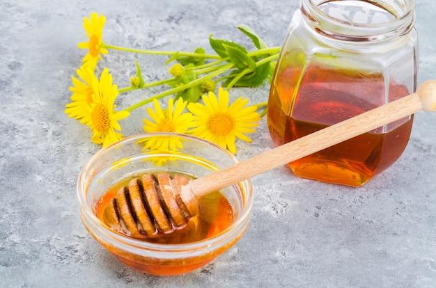 Aromatic flower honey, wild flowers on gray background.
