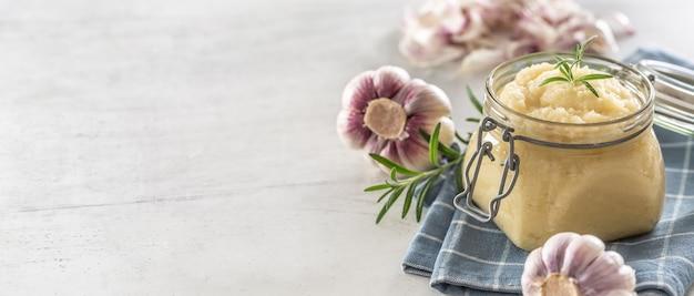 球根と皮をむいたクローブとローズマリーが付いている素朴な台所の布の上に置かれたガラスの瓶の中の芳香性のニンニクペースト。