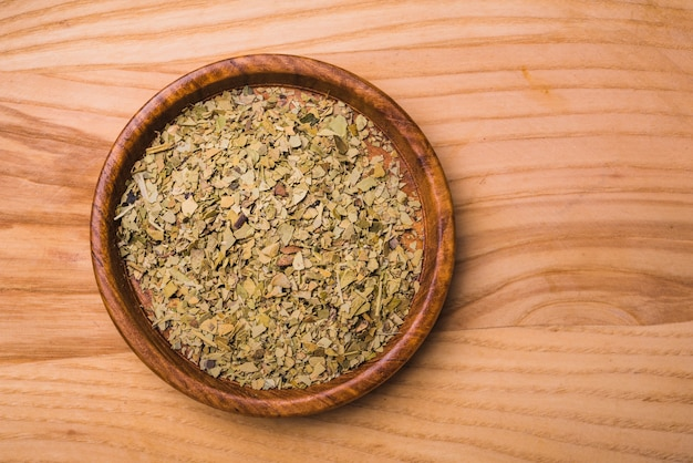 Aromatic green dry tea leaves on plate against wooden background