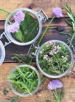 Ароматические травы в стеклянной банке, листья и цветы чеснока на столе