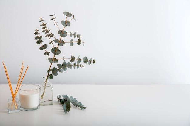 テーブルの上の白い壁に花瓶に芳香剤の家庭用香水スティック、線香、芳香剤キャンドル、ユーカリの枝の花束。コピースペースを備えたホームインテリアコンフォートエレメントとアロマテラピー