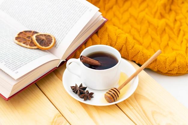 Ароматный горячий чай с корицей, покрытый теплым шарфом на деревянном осеннем фоне. ковшик с медом. комфортно читать книгу