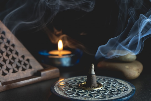 Aromatic incense next to a burning candle