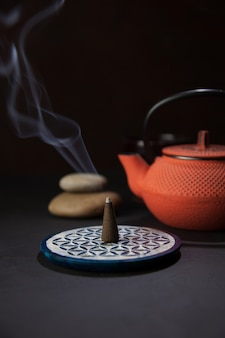 Aromatic incense cone next to a japanese iron teapot