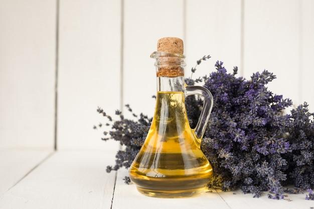 体の皮膚を回復させるためのスパ手順用の芳香性ラベンダーオイル。ラベンダーの花束の上のオイルのボトル。