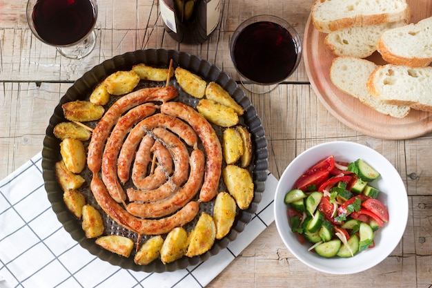 Aromatic meat sausages with potatoes, salad and wine on a wooden table.