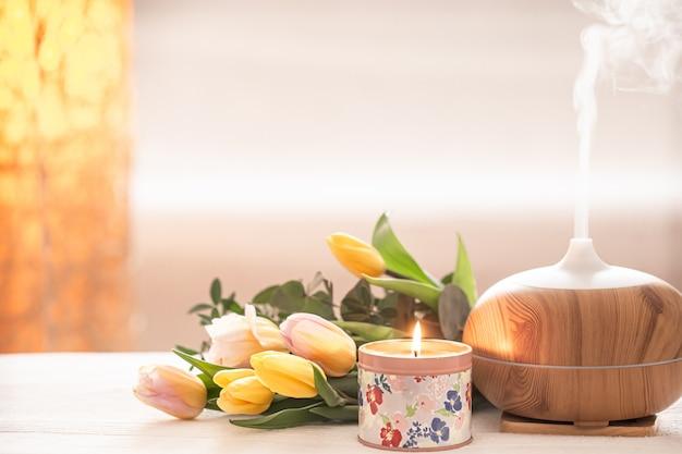 Ароматический масляный диффузор на столе размывается красивым весенним букетом тюльпанов и зажженными свечами.