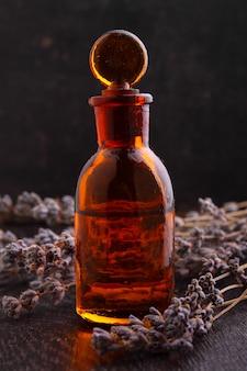 Ароматические масла с веткой лаванды на темном фоне