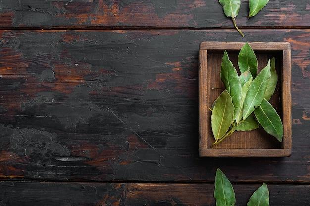 향기로운 유기 베이 잎, 나무 상자, 오래 된 어두운 나무 테이블 배경, 평면도, 평면 누워, 텍스트 복사 공간