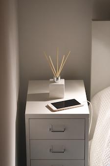 自宅のベッドサイドテーブルで芳香族リードの芳香剤とスマートフォンを充電。