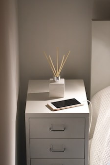 Aromatic reed air freshener and smartphone on charge on the bedside table at night at home.