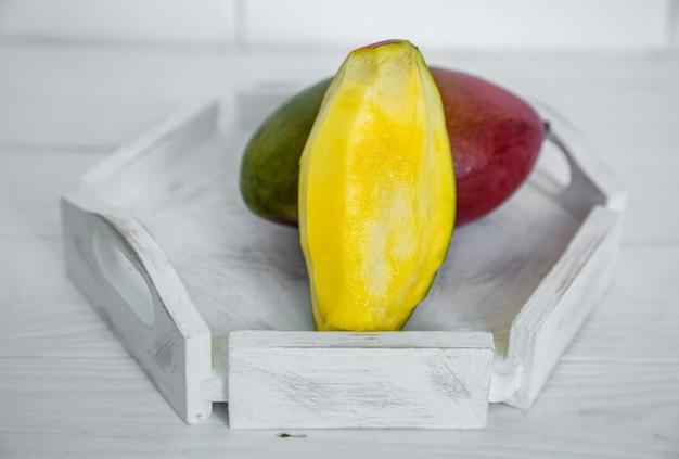 白い木製の背景、健康食品、エキゾチックなフルーツのコンセプトに芳香の熟したマンゴー