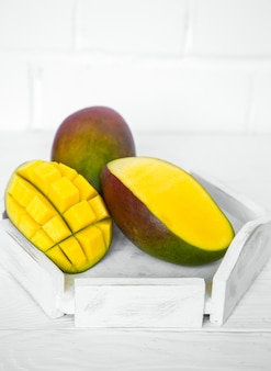 Ароматные спелые манго на белом деревянном фоне, концепция здорового питания и экзотических фруктов