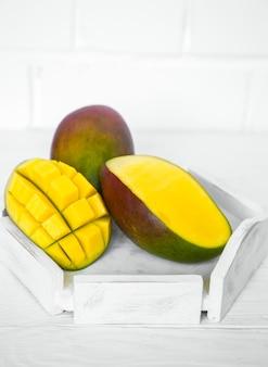 Mango aromatico maturo su fondo di legno bianco, concetto di cibo sano e frutta esotica