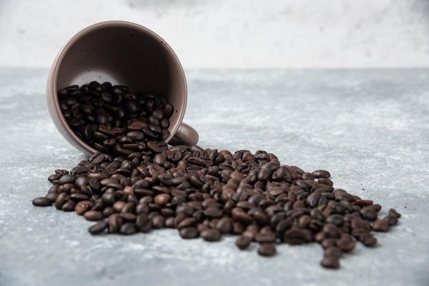 Chicchi di caffè tostati aromatici dalla tazza sulla superficie di marmo.