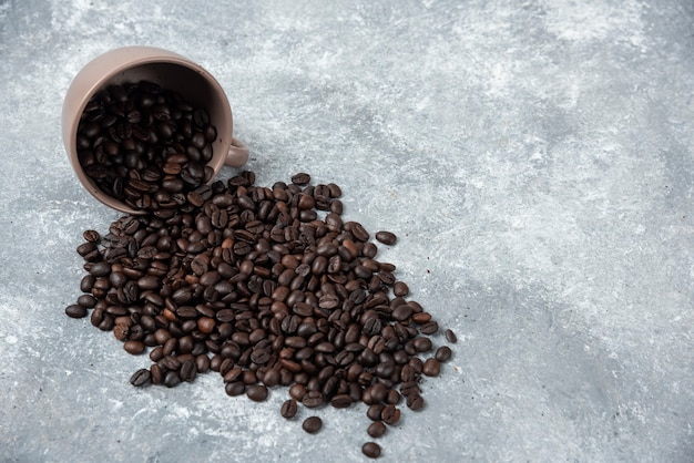 Aromatic roasted coffee beans out of cup on marble surface.