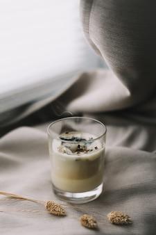 Ароматическая ароматическая свеча с дымом и засушенными цветами на бежевом текстиле