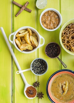Aromatic spices and dishes on green tabletop