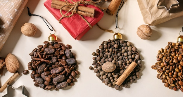 크리스마스 공 모양과 베이지색 종이 배경 위에 친환경 크리스마스 선물 상자로 향기로운 향신료 수집 및 다른 커피 콩. 크리스마스 인사 커피 애호가. 배너 크기
