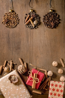 어두운 나무 배경 위에 크리스마스 공 모양과 친환경 크리스마스 선물 상자로 향기로운 향신료 수집과 다른 커피 콩. 크리스마스 인사 커피 애호가