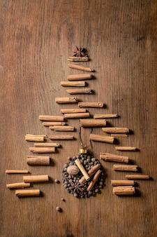 크리스마스 공 모양으로 향기로운 향신료 컬렉션과 크리스마스 트리로 계피 스틱. 올스파이스, 계피 스틱, 정향, 육두구는 어두운 나무 배경 위에 있습니다. 크리스마스 인사말 카드