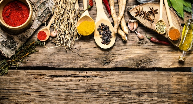 Aromatic spices and herbs on a rustic background. on wooden background. free space for text . top view