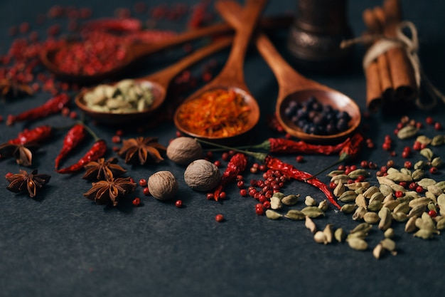 Aromatic spices in wood spoons on dark stone table