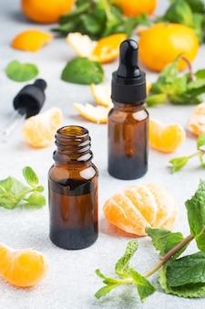 暗い泡の中の芳香族タンジェリンオイル、明るい灰色の背景のマンダリンからの化粧品オイル、コピースペース。