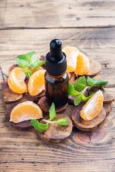 暗い泡の中の芳香族タンジェリンオイル、木製のマンダリンからの化粧品オイル