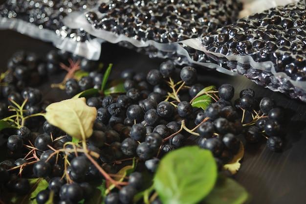 Ягоды черноплодной рябины (aronia melanocarpa) упакованы в вакуумные пакеты и черные ягоды на темном столе.