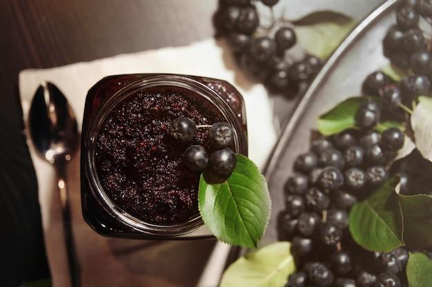 Варенье из черноплодной рябины (aronia melanocarpa) и ее ягод на темном столе. домашние консервы.
