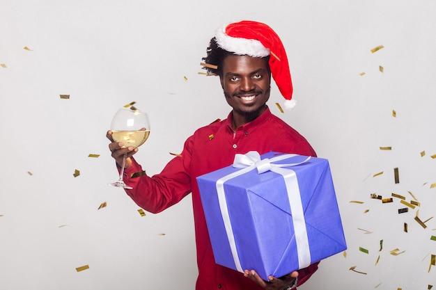 행복 주위에 빨간 모자를 쓴 남자, 황금 메타판, 샴페인 잔과 선물 상자를 들고 카메라를 보고 이빨이 웃는 남자가 날아갑니다. 스튜디오 촬영. 회색 배경