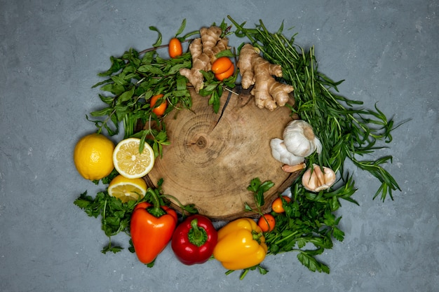 Around round wooden board set of fresh vegetables citrus and ginger on grey top view
