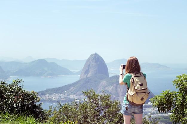 Вокруг света. девушка турист фотографирует на смартфон пао де акукар. рио де жанейро.