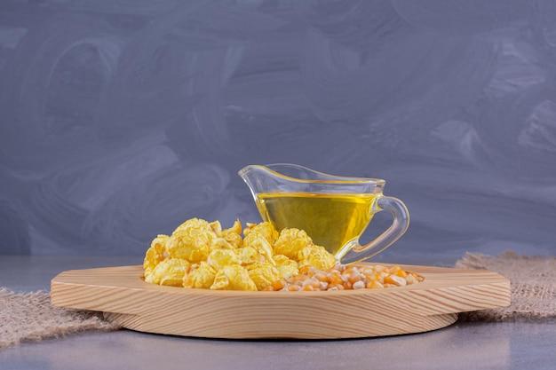 Композиция из карамельного попкорна, стакана масла и кукурузных зерен на деревянной тарелке на мраморном фоне. фото высокого качества