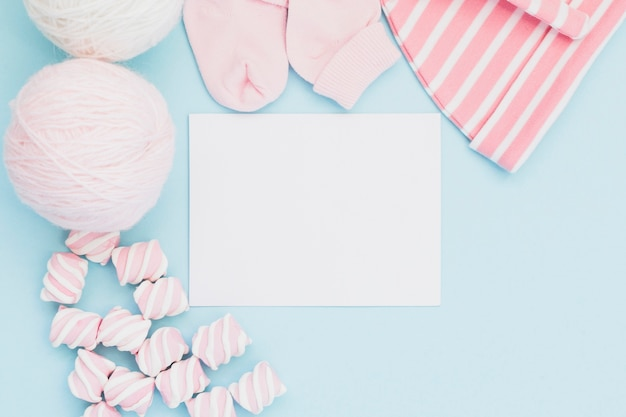 Arranged baby clothes and greeting card