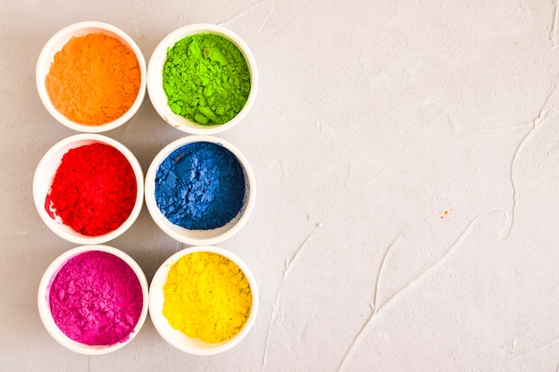 Arranged bowls of holi color powder on concrete backdrop
