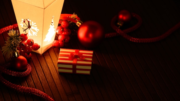 Arranged christmas adornments and small present box in light of lantern.