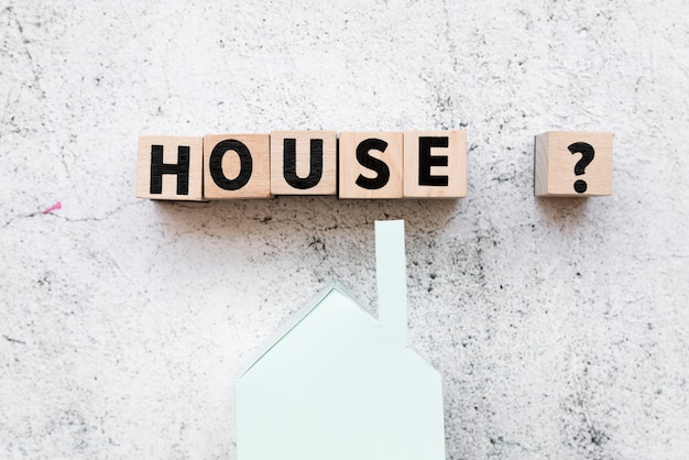 Arranged house text blocks with question sign over the paper house model against concrete backdrop