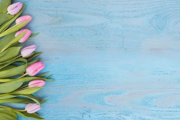 Arranged soft tulips on wood