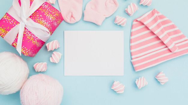 Arrangement of baby clothes and postcard