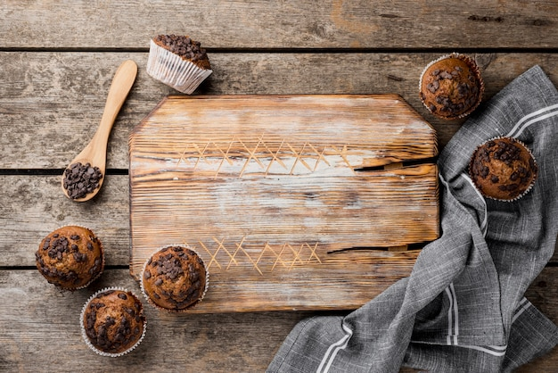 Arrangement of baked muffins and wooden board