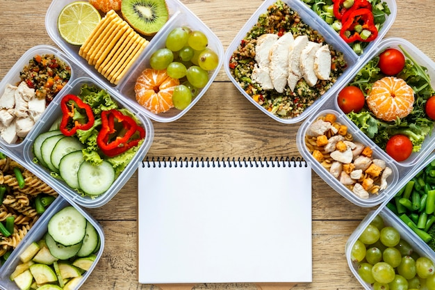 Arrangement of batch food cooked with empty notebook