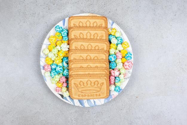 Un arrangiamento di biscotti e caramelle popcorn su un piatto su sfondo di marmo. foto di alta qualità