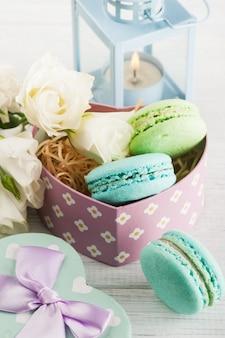 Arrangement of blue lanter, flowers, macaroons
