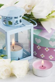 Arrangement of blue lanter, flowers, pastel gift box