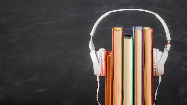 Arrangement of books with headphones with copy space