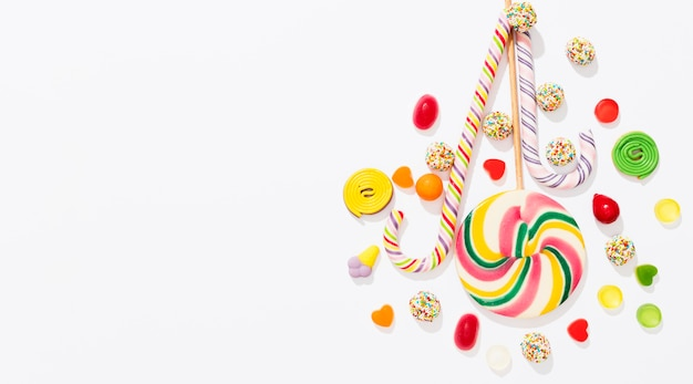 Arrangement of candies on white background with copy space