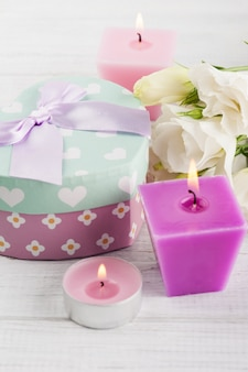 Arrangement of candles, flowers, pastel gift box