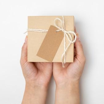 Disposizione della scatola di cartone con corda e tag vuoto